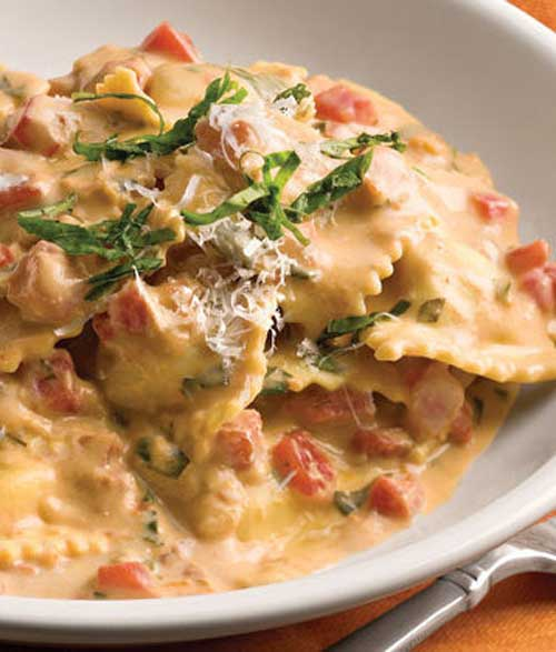 Recipe for Tuscan Pasta With Tomato Basil Cream - This elegant pasta dinner will have your family thinking you worked in the kitchen all day long. The secret, though, is refrigerated ravioli and jarred alfredo sauce that's heated with white wine, chopped fresh tomatoes, and fresh basil. Top with grated Parmesan cheese for a tasty finishing touch.