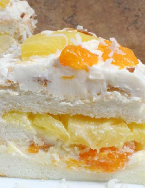 Recipe for Ambrosia Cake - An angel food cake with lots of fresh flavor. The pineapple, mandarin oranges, and toasted coconut give this cake recipe a tropical flair.