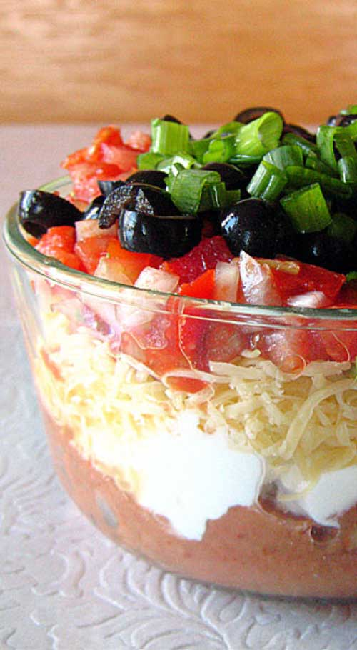 Recipe for Tex-Mex Seven Layer Dip - Without a doubt, my favorite party food is seven layer dip. With one deft swoop of a wide-brimmed tortilla chip, you can shovel seven unique tastes and textures into your open mouth at once.