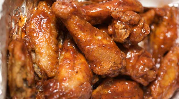 Recipe for Lightened-up Sweet and Spicy Chicken Wings - Wings are easy to make at home, and baking them in the oven cuts down on the fat and grease. Impress your friends with our sweet and spicy homemade version.