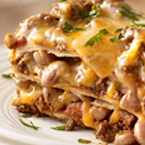 Recipe for Our Favorite Mexican-Style Lasagna - Create a little fusion with ooey-gooey cheese, beans and taco beef layered up and baked like lasagna.