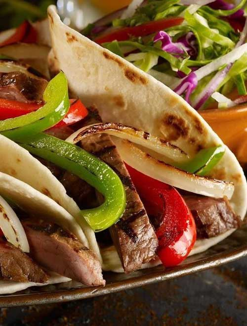 Recipe for Steak Fajitas - Classic Tex Mex, fajitas are typically made with grilled flank steak with onions and bell peppers, and served sizzling hot with fresh tortillas, guacamole, sour cream, and salsa.
