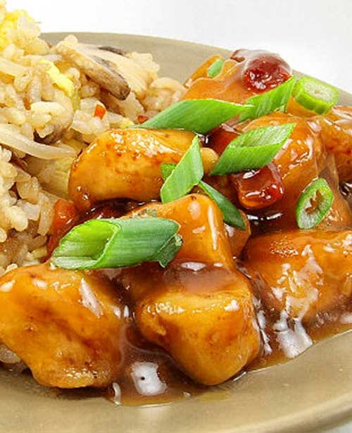 Spicy and sweet orange chicken is served with vegetable fried rice. You may never order take-out again!