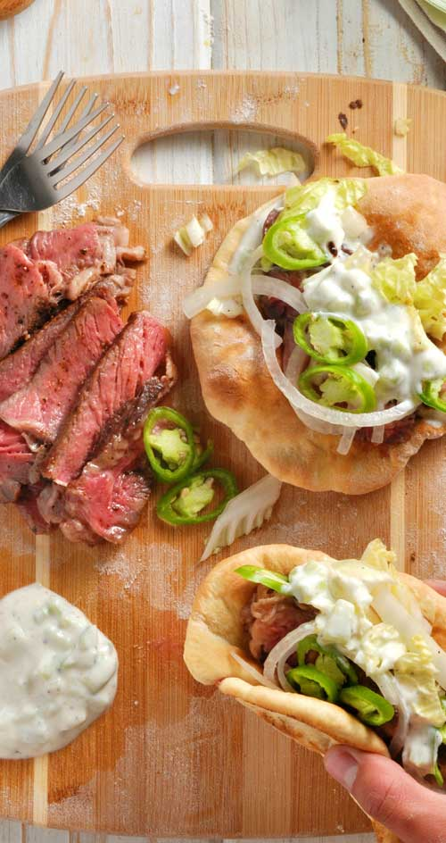 As summer peaks around the corner, you\'re going to want this Easy Steak Gyros with Homemade Pitas recipe in your arsenal for those sunny beach day picnics. #gyros #greekfood #steak #pitas #sandwiches